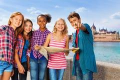 Grupo de niños con el mapa que se coloca en el terraplén Fotos de archivo