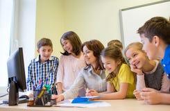 Grupo de niños con el profesor y el ordenador en la escuela imagen de archivo libre de regalías