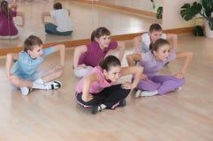 Grupo de niños contratados al entrenamiento físico. foto de archivo