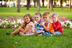 Grupo de niños de la diversión en la hierba verde. Foto de archivo
