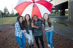 Grupo de niños debajo de un paraguas en la lluvia Foto de archivo