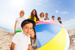 Grupo de niños detrás del parasol de playa Fotografía de archivo libre de regalías