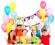 Grupo de niños en la fiesta de cumpleaños con las manos aumentadas Foto de archivo libre de regalías