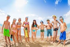 Grupo de niños en los trajes de baño que se colocan en la playa arenosa Imagen de archivo libre de regalías