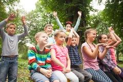 Grupo de niños en un banco de parque Imagenes de archivo