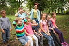 Grupo de niños en un banco de parque Foto de archivo