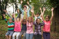 Grupo de niños en un banco de parque Imagen de archivo