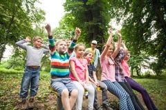 Grupo de niños en un banco de parque Fotos de archivo libres de regalías