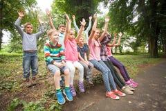 Grupo de niños en un banco de parque Foto de archivo libre de regalías