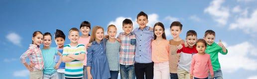 Grupo de niños felices que abrazan sobre el cielo azul Imagen de archivo libre de regalías