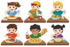 Grupo de niños felices que comen la comida deliciosa