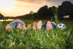 Grupo de niños felices que mienten en la hierba Foto de archivo libre de regalías