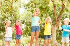 Grupo de niños felices que muestran los pulgares para arriba Imágenes de archivo libres de regalías