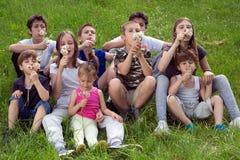 Grupo de niños felices que se divierten al aire libre, sentándose en la hierba y soplando las flores del diente de león en Sunny  Imágenes de archivo libres de regalías