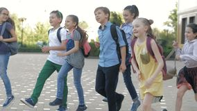 Grupo de niños felices que vuelven de escuela junto metrajes