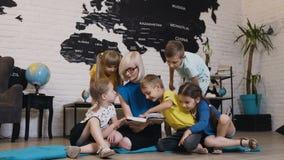 Grupo de niños hermosos que hablan del libro con el profesor del cuarto de niños en preescolar Trabajador feliz del cuidado de dí metrajes