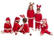 Grupo de niños lindos en jugar rojo del traje de la Navidad imagen de archivo