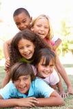 Grupo de niños llenados para arriba en parque Imágenes de archivo libres de regalías