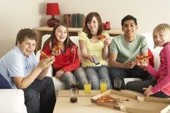 Grupo de niños que comen la pizza que ve la TV Imagen de archivo libre de regalías