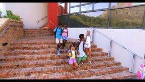 Grupo de niños que consiguen abajo de escalera almacen de metraje de vídeo