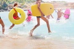 Grupo de niños que corren en el mar para nadar fotos de archivo
