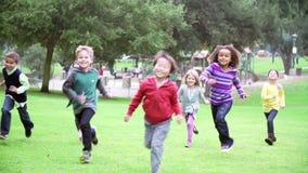 Grupo de niños que corren hacia cámara en la cámara lenta