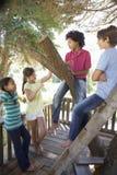 Grupo de niños que cuelgan hacia fuera en casa del árbol junto imagen de archivo