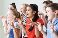 Grupo de niños que gozan del club del drama junto imagen de archivo