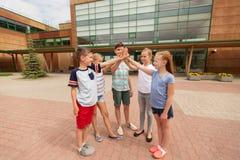 Grupo de niños que hacen el alto cinco en el patio de escuela Fotos de archivo