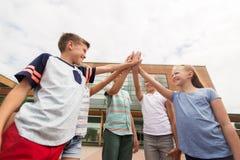 Grupo de niños que hacen el alto cinco en el patio de escuela Imagen de archivo libre de regalías