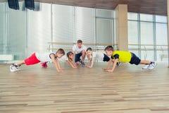 Grupo de niños que hacen la gimnasia de los niños en gimnasio con el profesor del cuarto de niños Fotos de archivo