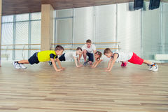 Grupo de niños que hacen la gimnasia de los niños en gimnasio con el teac del cuarto de niños Fotos de archivo libres de regalías