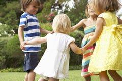 Grupo de niños que juegan al aire libre junto Imagenes de archivo