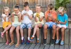 Grupo de niños que juegan con los teléfonos móviles al aire libre Fotografía de archivo libre de regalías