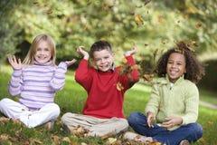 Grupo de niños que juegan en hojas Imágenes de archivo libres de regalías