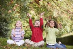 Grupo de niños que juegan en hojas de otoño Imagen de archivo