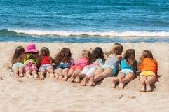 Grupo de niños que mienten en la playa Imagen de archivo libre de regalías