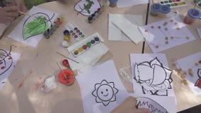 Grupo de niños que pintan en escuela metrajes