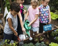 Grupo de niños que riegan las plantas fotos de archivo