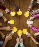Grupo de niños que se inspiran y que comparten ideas con la bombilla Foto de archivo