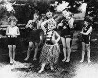 Grupo de niños que se realizan con los instrumentos y una muchacha que bailan el hula (todas las personas representadas no son vi Fotografía de archivo libre de regalías