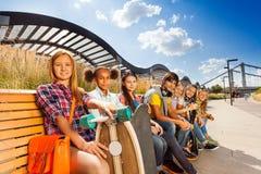 Grupo de niños que se sientan en banco de madera junto Imágenes de archivo libres de regalías