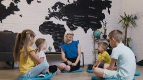 Grupo de niños que se sientan en el piso en círculo alrededor del profesor y que estudian la geografía en sala de clase de la geo metrajes