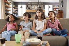 Grupo de niños que se sientan en Sofa Watching Television Together imagenes de archivo