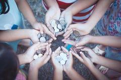 Grupo de niños que sostienen el dinero en manos en el círculo junto fotografía de archivo