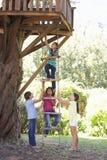 Grupo de niños que suben la escalera de cuerda a la casa del árbol foto de archivo libre de regalías