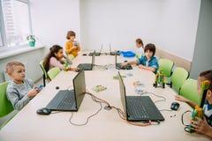 grupo de niños serios que trabajan con los ordenadores foto de archivo libre de regalías
