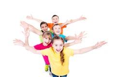 Grupo de niños sonrientes con las manos aumentadas Imagenes de archivo