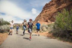 Grupo de niños sonrientes que corren junto al aire libre imagen de archivo