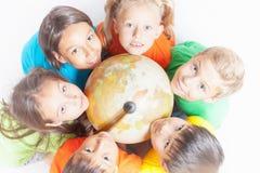 Grupo de niños internacionales que sostienen la tierra del globo Imágenes de archivo libres de regalías